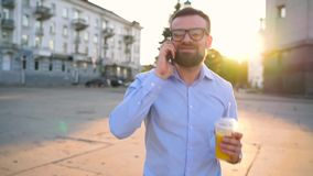 Man talking on smartphone and drinking juice walking down the street stock footage