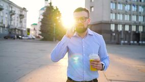 Man talking on smartphone and drinking juice walking down the street, slow motion stock video
