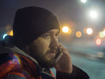 Man talking by smartphone at night bokeh light in background. Concept of night shift Royalty Free Stock Photography