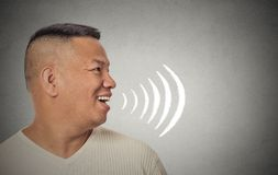 Man talking with sound waves coming out of his open mouth. Side profile portrait young man talking with sound waves coming out of his open mouth isolated grey Royalty Free Stock Photography