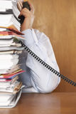 Man Talking On Telephone Behind A Stack Of Folders Royalty Free Stock Photo
