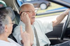 Man talking on telephone while driving being reprimanded by wife. Man Royalty Free Stock Photos