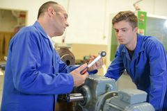 Man talking to apprentice holding socket wrench. Man stock photos