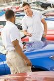 Man talking to car salesman. On lot royalty free stock photo