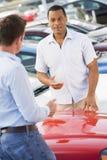 Man talking to car salesman. At lot Stock Image