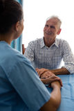 Man talking to female doctor at table in retirement home. Senior men talking to female doctor at table in retirement home Stock Photos