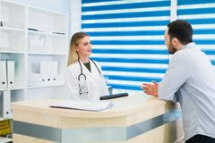 Man talking to female receptionist at hospital.  Royalty Free Stock Images