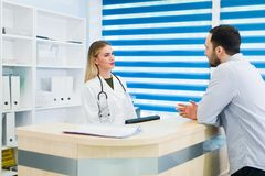Man talking to female receptionist at hospital Stock Photos