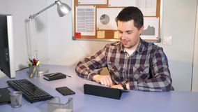 A man is talking to his friend on the tablet during his working break. A young man talking to his friend on the tablet during his working break. Office worker stock footage