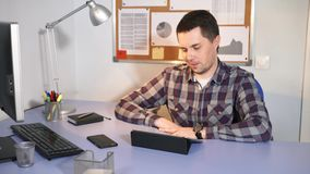 A man is talking to his girlfriend on the tablet during his working break. A young man talking to his girlfriend on the tablet during his working break. Office stock video footage