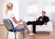 Man talking to his psychiatrist Stock Images