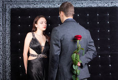 Man Talking to a Lady with Rose on his Back Stock Photography