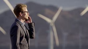 A man talking to the phone in the countryside. With windmills on the background stock video