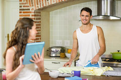 Man talking to woman while ironing a shirt Royalty Free Stock Photography
