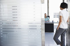 Man Talking To Woman Standing In Office Doorway Stock Photography