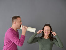 Man talking through  tube and a woman plugging her ears Royalty Free Stock Photography