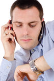 Man talking on two cellphones and looking at watch Stock Image
