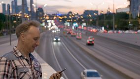 Man talks on mobile phone against evening city sunset sky. MOSCOW/RUSSIA - MAY 20 2019: Man in checkered shirt talks on mobile phone by tunnel underpass parapet stock footage