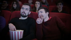 Man talks out loud with man in cinema stock video footage