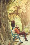 Man talks on phone. Bearded men hipster talks on phone on bench with pretty girl outdoors in autumn park with yellow leaves on natural background stock image