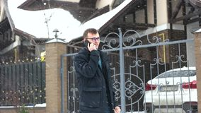 Man talks the phone near the expensive car. In snow weather stock footage