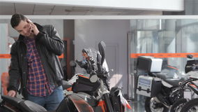 Man talks on the phone near motorbike. Consultant talking on the phone near black motorbike. Smiling guy standing near the motorcycle and looking at it stock video footage