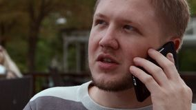 4K Closeup shot. A man talks on the phone by sitting in a cafe outdoors stock video footage