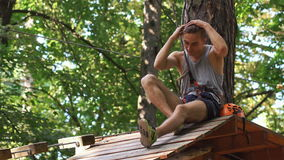 Man talks on the phone sitting on the tree in an entertainment park stock footage