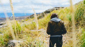 Man in tall grasses along coastline Royalty Free Stock Image