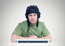 Man in a tank helmet at the computer keyboard Royalty Free Stock Photo