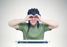 Man in a tank helmet looks through fingers like binoculars Stock Photos