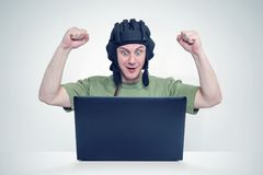 Man in tank helmet playing in game, sitting front of laptop. Concept of winner Royalty Free Stock Photography