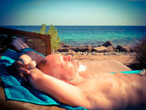 Man Tanning on the Beach Royalty Free Stock Photos