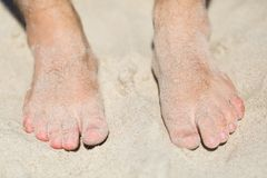 Man tanning on beach sand. Close up of foot. Royalty Free Stock Image