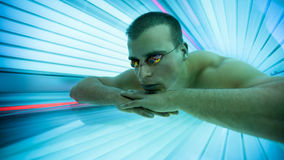 Man tanning bed in solarium. Man with protect glasses on tanning bed in solarium stock images