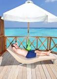 Man tans on  water villa  terrace on ocean Stock Photo