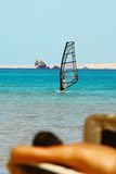 Man tans on windsurfing background. Man tans on windsurfer, blue sea and transparent sail background stock photography