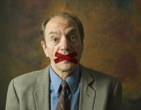 Man with tape across mouth Royalty Free Stock Photos