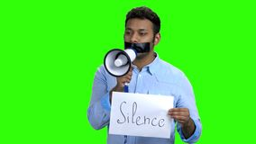 Man with tape on mouth holding megaphone. Young dark-skinned man with taped mouth holding card with inscription Silence stock video