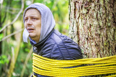 Man with tape on mouth tied to the tree Royalty Free Stock Image