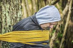 Man with tape on mouth tied to the tree Stock Image
