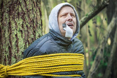 Man with tape on mouth tied to the tree Stock Photo