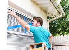 Man Taping His Windows. Man taping the windows on his home to protect from broken glass in a hurricane stock images