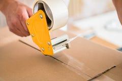 Man taping packing case Stock Photo
