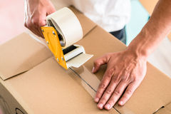 Man taping packing case Stock Photography