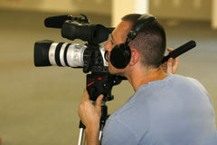 Man taping with video camera. A young man videotaping with a high end video camera Royalty Free Stock Photo