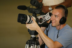 Man taping with video camera. A young man videotaping with a high end video camera Royalty Free Stock Photography