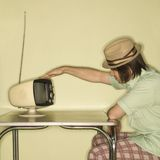 Man tapping old television. Royalty Free Stock Photography