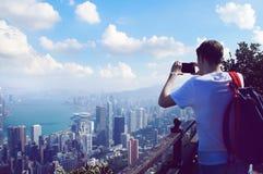 Man tar ett telefonfoto av Hong Kong byggnadspanorama Royaltyfri Fotografi