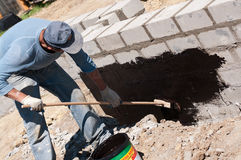 Man tarring a house foundation Stock Photos